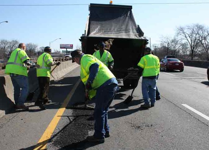 Five workers patching potholes on the highway